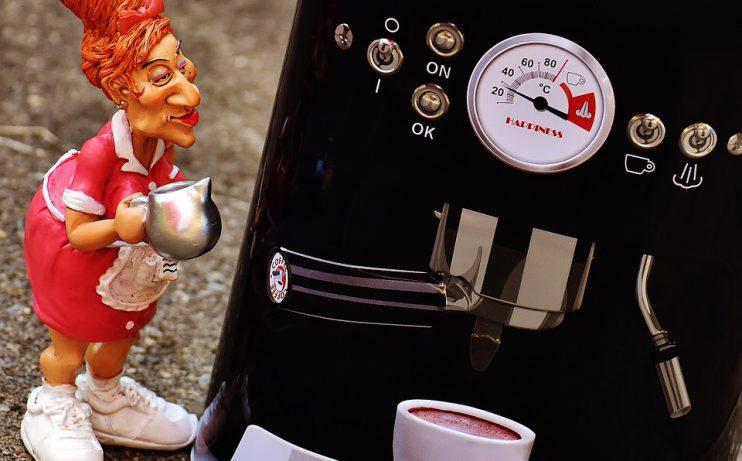 Mevrouw zet koffie met een koffiemachine.